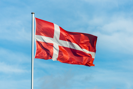 Closeup of single danish flag waving in the wind in front of blue sky