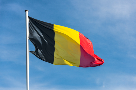 Closeup of single belgian flag waggling in the wind in front of blue sky