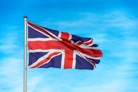 Closeup of single british union jack flag waving in the wind in front of blue sky Stock Photo