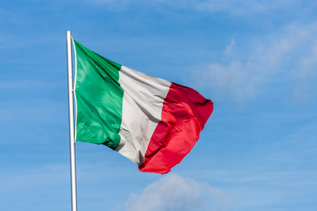 Closeup of single italian tricolor flag waving in the wind in front of blue sky Stock Photo