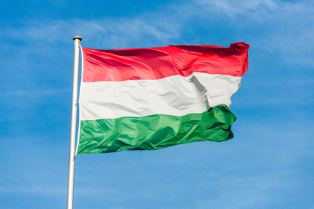 Closeup of single hungarian tricolor flag waving in the wind in front of blue sky Foto de archivo