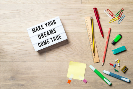 Make your dreams come true writing in lightbox with pen, pencil, highlighter and ruler lying on office desk as flat lay