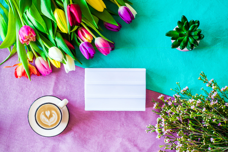 Happy Easter spring shot from above as flatlay with blank light box for message and colorful tulips, flowers and coffee cup