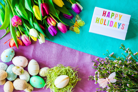 Shot from above as flatlay with happy holidays message written on light box and colorful retro easter eggs, tulips and flowers