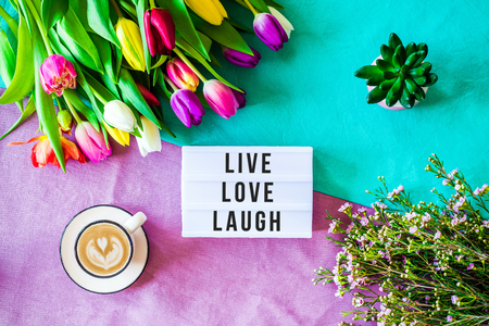 Shot from above as flatlay with live love laugh message written on light box with coffee and colorful tulips and flowers