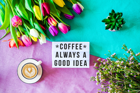 Shot from above as flatlay with coffee always a good idea message written on light box with coffee and colorful tulips and flowers Stock Photo