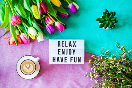 Shot from above as flatlay with relax,  enjoy, have fun message written on light box with coffee and colorful tulips and flowers Stock Photo