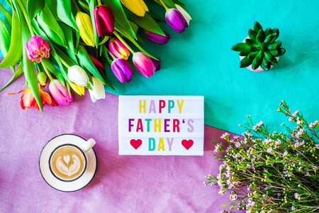 Shot from above as flatlay with happy fathers day message written on light box with coffee and colorful tulips and flowers