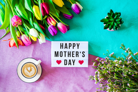 Shot from above as flatlay with happy mothers day message written on light box with coffee and colorful tulips and flowers