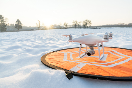 Photo of a white professional quadcopter drone camera standing on heliport with white snow in winter in front of forest Stock Photo
