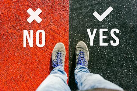 Llegar a una encrucijada teniendo que decidir sobre no y sí sobre el futuro simbolizado por dos pies de pie en dos colores diferentes en el camino desde arriba Foto de archivo