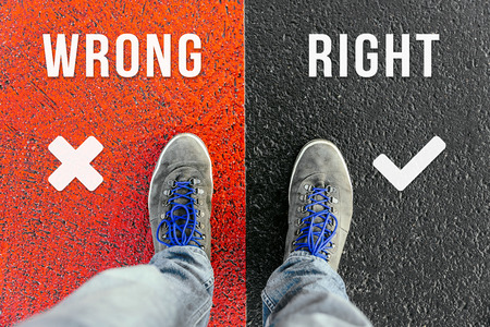 Reaching a crossroads having to choose between wrong and right and about future symbolized by two feet standing on two different colors with arrows on pathway from above