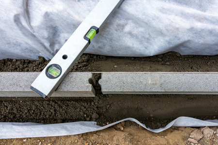 Setting edge restraints buy putting border curb stones in earth-moist concrete with bubble level Stock Photo