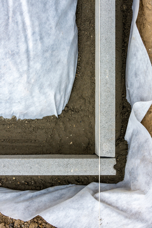 Setting edge restraints buy putting border curb stones in earth-moist concrete Stock Photo