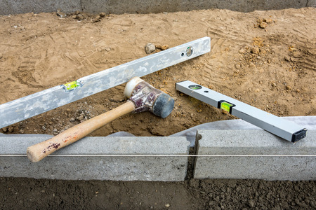 Setting edge restraints buy putting border curb stones in earth-moist concrete with rubber mallet and bubble level