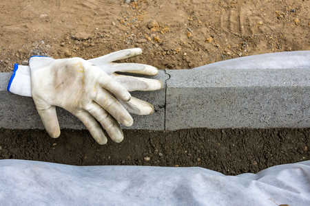 Setting edge restraints buy putting border curb stones in earth-moist concrete with two gloves