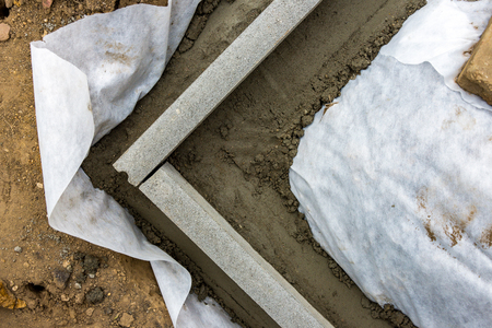 Setting edge restraints buy putting border curb stones in earth-moist concrete Stock Photo