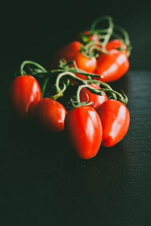 Closeup of healthy vibrant shiny red tomatoes as food photograhpy against black shale background
