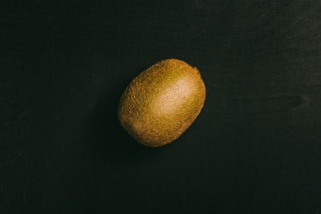 Kiwi fruit lying on black chalkboard in background with copy space from above as flat lay
