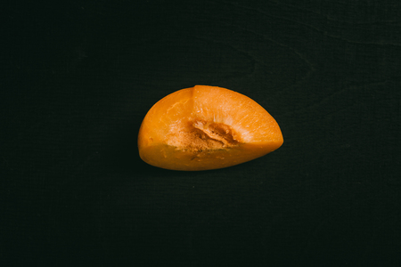 Cut peach with seed lying on black chalkboard in background with copy space from above as flat lay 写真素材