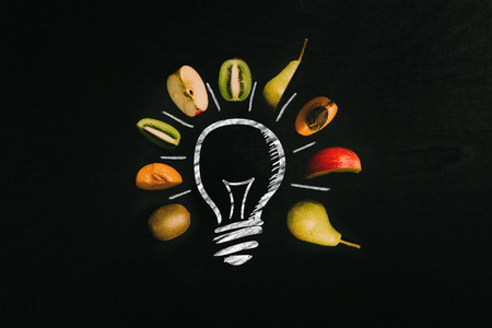 White light bulb painted on black chalkboard surrounded by fresh healthy cut colorful fruits with free space as template 写真素材