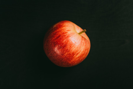 Vibrant colored apple lying on black chalkboard in background with copy space from above as flat lay