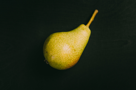 Vibrant colored pear lying on black chalkboard in background with copy space from above as flat lay 写真素材