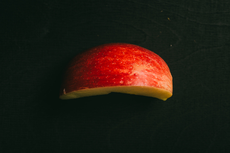 Cut apple lying on black chalkboard in background with copy space from above as flat lay