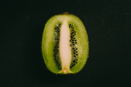 Cut kiwi fruit lying on black chalkboard in background with copy space from above as flat lay