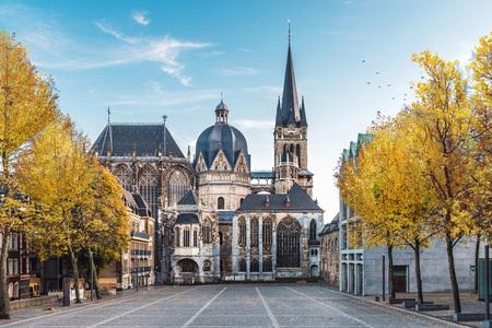 Riesiger gotischer Dom in Aachen Deutschland im Herbst mit gelben Bäumen am Katschhof gegen blauen Himmel im Hintergrund