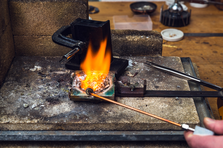 Melting down of brass metal with a torch flame in a crucible at working place of goldsmith for performing handicraft metalwork