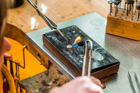 Goldsmith working and soldering an unfinished jewelry piece with a torch flame at a workbench in workshop