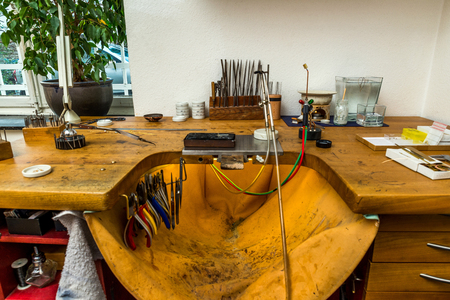 Equipment and tools of a goldsmith with polisher, tongs, pincers on wooden working desk inside a workshop in the background 写真素材