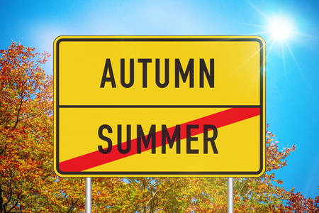 Yellow roadsign or place-name sign with autumn and summer written on it and summer being crossed out against sunny sky with colorful fall foliage in background