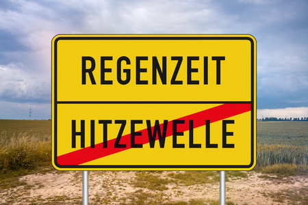Yellow roadsign or place-name sign with rainy period and heat wave written in german and heat wave being crossed out against cloudy sky and field in background