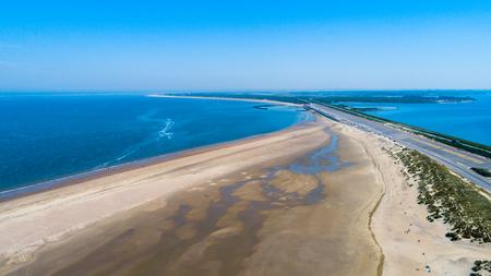 Luchtfoto genomen op een strand en blauwe zee als kust van Zeeland in Nederland