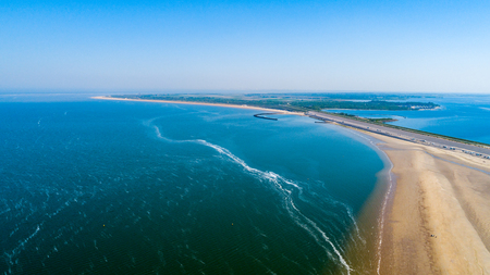 Aerial view taken by a drone at a beach and blue sea as seaside from zeeland in the Netherlands
