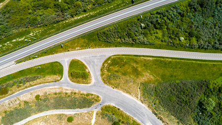 Curved road and bicycle lane surrounded by green grass and trees taken from above with drone