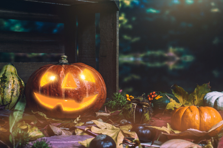 Moody scary carved halloween pumpkin with colorful leaves and chestnuts as background for thanksgiving Zdjęcie Seryjne