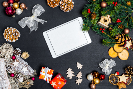 Christmas decoration and white tablet with copy space for happy new year message against black background as flatlay