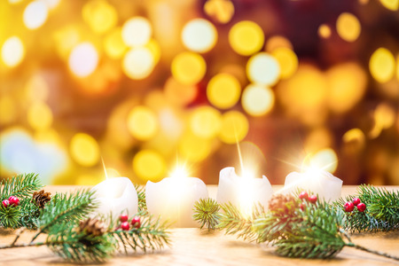 Four ignited advent candles with bokeh lights in background surrounded by christmas fir branches 写真素材 - 110559389