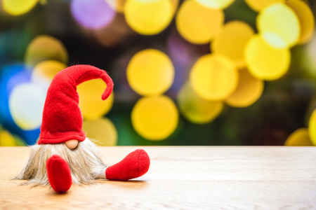 Christmas elf with bokeh lights in background surrounded by christmas decorations  Imagens