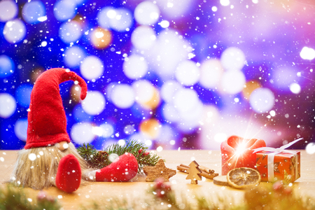 Red sitting christmas elf in falling snow with bokeh lights in background surrounded by christmas decorations as gift box and ignited advent candle
