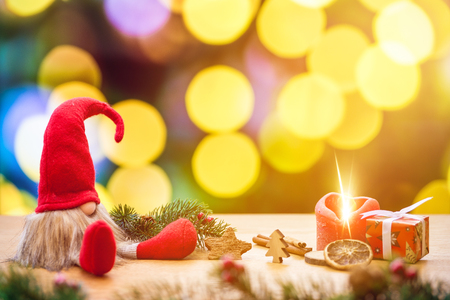 Red sitting christmas elf with bokeh lights in background surrounded by christmas decorations as gift box and ignited advent candle