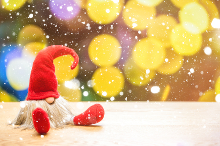 Red sitting christmas elf in falling snow with bokeh lights in background