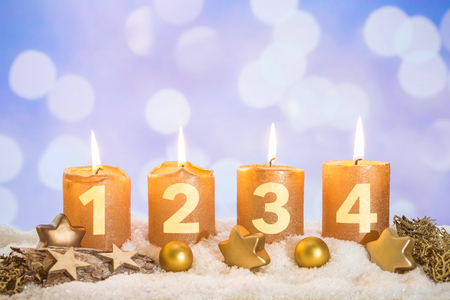 Four numbered gold advent candles with four candles lit and christmas decoration lying in snow as template