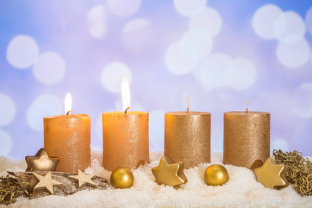 Four golden advent candles with two candles lit and christmas decoration lying in snow as template