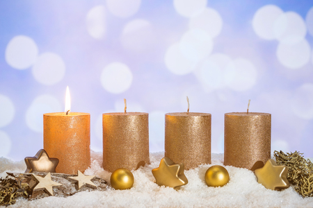 Four golden advent candles with first candle lit and christmas decoration lying in snow as template Imagens