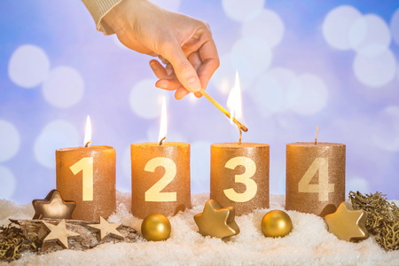 Four numbered gold advent candles with three candles lit by hand with match and christmas decoration lying in snow as template