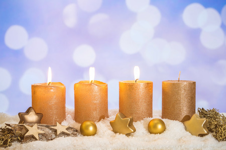 Four golden advent candles with three candles lit and christmas decoration lying in snow as template